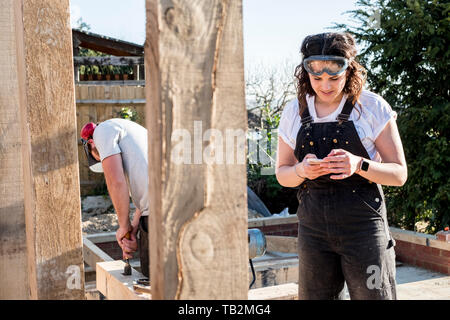 Smiling woman wearing dungarees and protective goggles standing on building site, checking her mobile phone. - Stock Photo