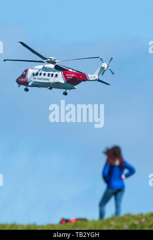 A Sikorsky S-92A HM Coastguard SAR Helicopter G-MCCZ operated by Bristol Helicopters flying overhead in England, UK. - Stock Photo
