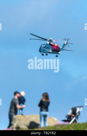 A Sikorsky S-92A HM Coastguard SAR Helicopter G-MCCZ operated by Bristol Helicopters flying low overhead in England, UK. - Stock Photo