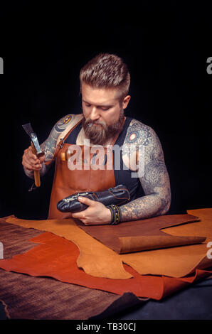 Currier of leather cutting out leather goods at the place of work - Stock Photo