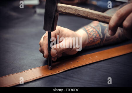 Handicraftsman processing a leather workpiece at the workshelf - Stock Photo