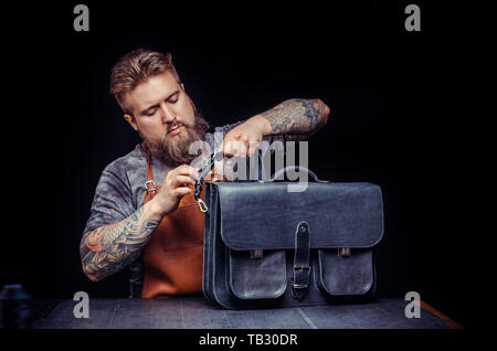 Leather Worker works with leatherwork at his workshop - Stock Photo