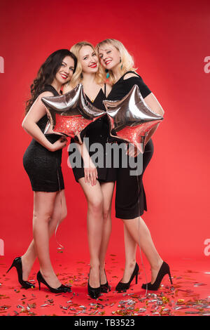 Three gorgeous ladies in evening dresses having fun on black background. - Stock Photo