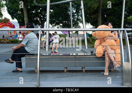 15.03.2019, Singapore, Singapore, Singapore - A young woman sits on a bench on the shore of Marina Bay and hugs a teddy bear. 0SL190315D006CAROEX.JPG  - Stock Photo