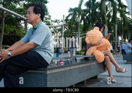 15.03.2019, Singapore, Singapore, Singapore - A young woman sits on a bench on the shore of Marina Bay and hugs a teddy bear. 0SL190315D009CAROEX.JPG  - Stock Photo