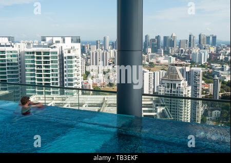12.02.2019, Singapore, , Singapore - A hotel guest looks out from the pool edge in the hotel pool of the Courtyard By Marriott Hotel onto the cityscap - Stock Photo