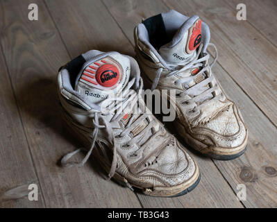 Pair of old worn 1990s Reebok Pump white basketball sneakers - Stock Photo
