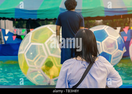 Mom and dad watching their son having fun in giant bubble ball on water in the swimming pool at the theme park in annual festival. - Stock Photo