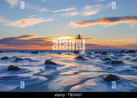 Monk on the abandoned military watching tower, orange sunset over frozen sea coast - Stock Photo