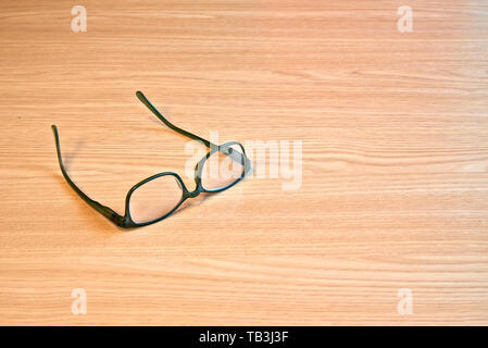 Textured wooden table and eyeglasses in close up view from above - Stock Photo