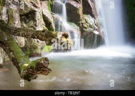 Close up view of a scenic, beautiful mountain waterfall cascading down the red, wet, rocky cliff and old tree branches covered by moss - Stock Photo