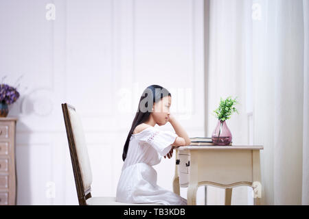Side View Of Sad Little Child Sitting On Floor Back To