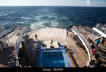 Passengers enjoy the sunshine on the aft outer decks of the Marco Polo in The North Atlantic Ocean - Stock Photo