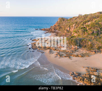 Beautiful aerial image of a seaside village with small beach and gentle blue waves - Stock Photo