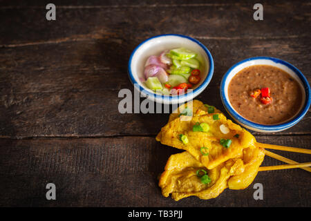 Pork satay with thai spices and peanut sauce placed on the wood table. - Stock Photo