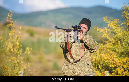 Hunting masculine hobby concept. Man brutal gamekeeper nature background. Hunter hold rifle. Bearded hunter spend leisure hunting. Focus and concentration of experienced hunter. Regulation of hunting. - Stock Photo