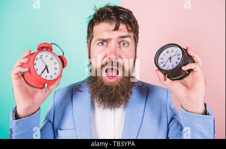 Does changing clock mess with your health. Man bearded hipster hold two different clocks. Guy unshaven puzzled face having problems with changing time. Changing time zones affect health. Time zone. - Stock Photo