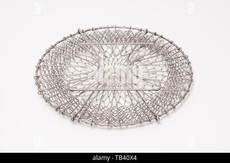 A flattened wire-mesh basket for steaming food. - Stock Photo