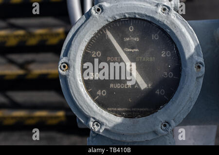 A ship rudder indicator, painted white with specs of paint on the glass, isolated to the rest of the ship, nobody in the image - Stock Photo
