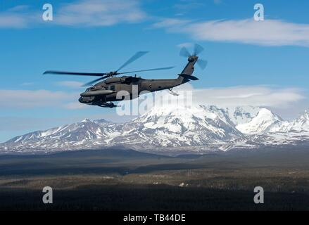 A UH-60 Black Hawk helicopter piloted by U.S. Army Chief Warrant Officer 3 Jeshua McMaster, Instructor pilot, and Chief Warrant Officer 2 Steven Mullins, rotary wing pilot, Bravo Company, 1st Battalion, 207th Aviation Regiment Bravo Company, fly from Juneau to Anchorage, Alaska, April 29, 2019.  Soldiers with the Alaska National Guard from 1-207th conduct cross-country training flights during their final annual training as an air assault unit ahead of a transition to general aviation support. (U.S. Army National Guard photo by 1st Lt. Benjamin Haulenbeek) - Stock Photo