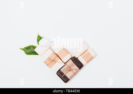 Organic natural handmade soaps of various types wrapped in brown paper next to green leaves on white background, flat lay. - Stock Photo