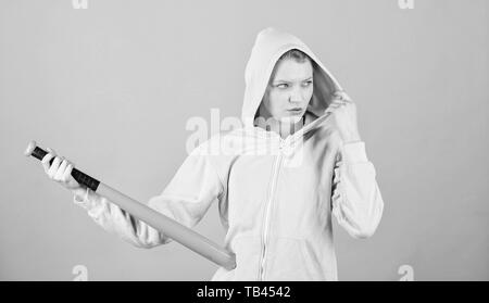 Woman play baseball game or going to beat someone. Girl hooded jacket hold baseball bat blue background. Woman in baseball sport. Baseball female player concept. Feeling power. She is dangerous. - Stock Photo