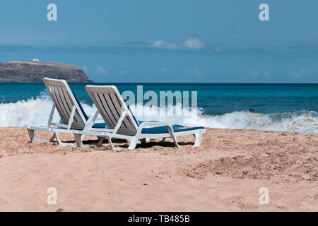 Two empty deck chairs on a deserted sandy beach on the ocean. - Stock Photo