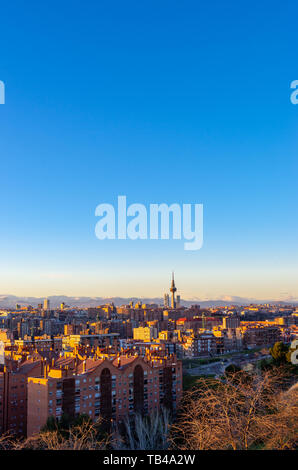 Skyline of Madrid at sunset with Sierra de Guadarrama range in background - Stock Photo