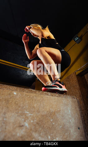Shot of a young woman jumping onto a box as part of exercise routine - Stock Photo