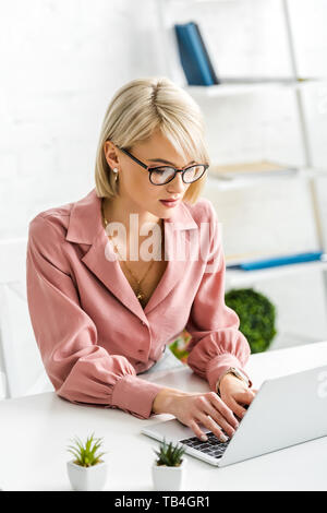 young blonde freelancer in glasses typing on laptop - Stock Photo