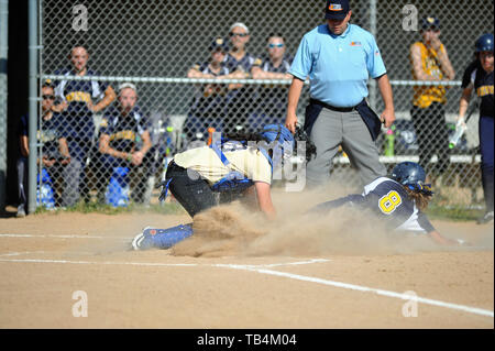 Catcher applying a tag to a sliding runner attempting to score as the home plate umpire looks on in advance of making a call. USA. - Stock Photo