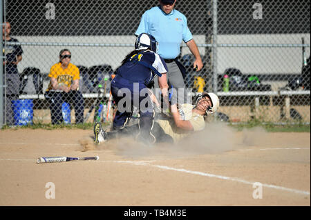 Catcher making a tag a base runner that was attempting to score. USA. - Stock Photo