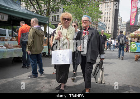 Two youthfull looking middle age women walk through the Union Square Green Market chatting and holding shopping bags. In New York City. - Stock Photo