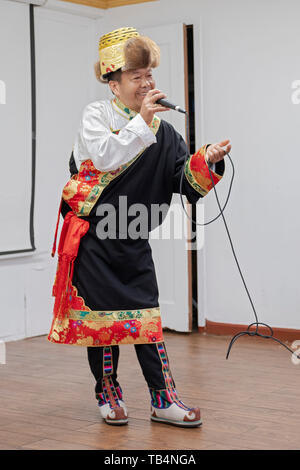 A Nepalese Buddhist man in a traditional costume sings Himalayan songs to seniors at the Sherpa Temple in Elmhurst, Queens, New York City. - Stock Photo