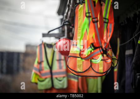 Personal protective equipments for sale on a shop: harness, reflective vests, yellow jackets, construction site helmets, as well as various other PPE  - Stock Photo