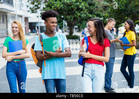 French female student and german guy and group of multiethnic students outdoor in city in summer - Stock Photo