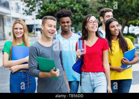 French female student and german guy with group of mutliethnic students outdoor in city in summer - Stock Photo