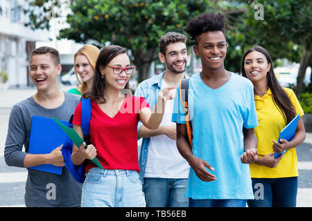 French female student and african american guy with group of mutliethnic students outdoor in city in summer - Stock Photo