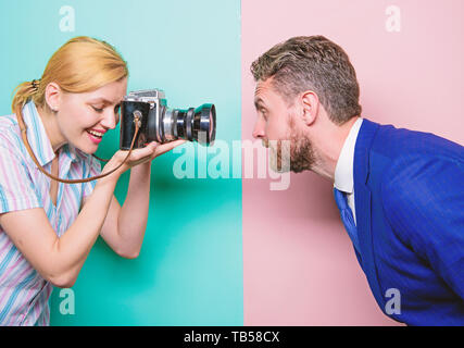 Enjoying photo shoot session. Photographer shooting male model in studio. Pretty woman using professional camera. Businessman posing in front of female photographer. Fashion shooting in photo studio. - Stock Photo