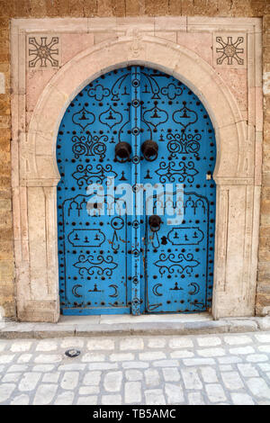 The traditional blue door of a 17th century house decorated with Islamic motifs in an alleyway of the medina (old city) of Tunis, Tunisia. - Stock Photo