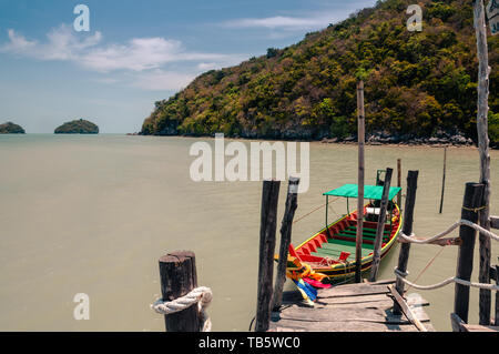 Wooden pier and thai long tail boat in Talet bay at Nakhon Si Thammarat province of Thailand. - Stock Photo