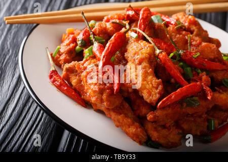 Chinese food chicken in Schezwan sauce close-up on a plate on the table. horizontal - Stock Photo
