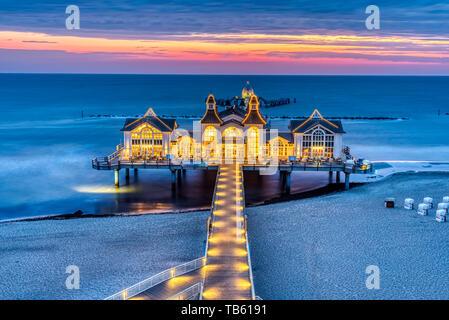 Sea pier with restaurant before sunrise seen on Ruegen island, Germany - Stock Photo