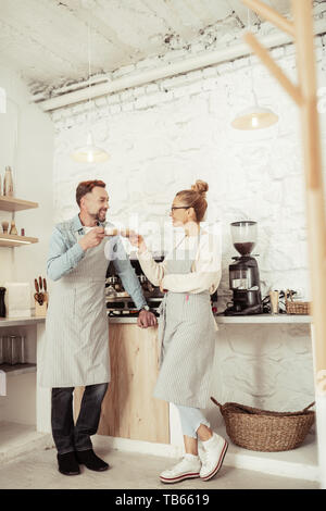 Clanging glasses. Two cheerful baristas wearing aprons standing in the kitchen and drinking coffee together. - Stock Photo