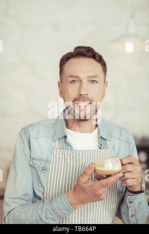 Look of happiness. Handsome happy man wearing apron holding his cup of fragrant coffee. - Stock Photo