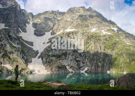 Gadsar, Kashmir, India- Dated- May 18, 2019: A hiker overlooking the turquoise blue waters of Gadsar lake with the source glacier in the background. G - Stock Photo