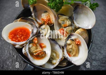 enamel venus shell cooking pan seafood plate with Shellfish Clams ocean gourmet dinner cooked with herbs and spices chilli sauce on dark background - Stock Photo