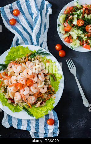 Delicious sauteed shrimp with cajun seasoning and lime on a maple plank white plate with salad and herbs on a black background, top view, closeup. Fre - Stock Photo