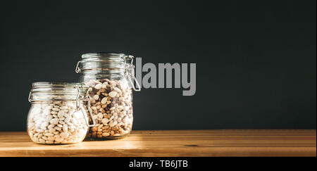 Various of kidney beans. Red, white and black kidney beans in wooden bowls with rosemary on grey concrete background. Copy space, banner. - Stock Photo