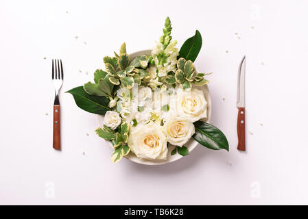 White flowers on plate, fork, knife over light background. Healthy eating, vegan diet concept. Creative layout. Top view, flat lay. - Stock Photo